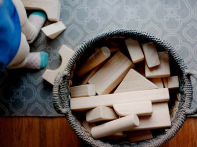 Baby playing with a basket of basic wooden block toys. Just baby's feet as they stand up after stacking.